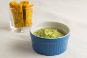 Schale mit 3 Minuten Avocado Dip und Gemüse-Pfannkuchen-Sticks im Hintergrund