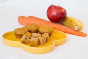 Banane Apfel Möhre Muffins ohne Zucker auf einem gelben Teller, ein Muffin in Stücke geschnitten, mit Banane, Apfel und Möhre im Hintergrund