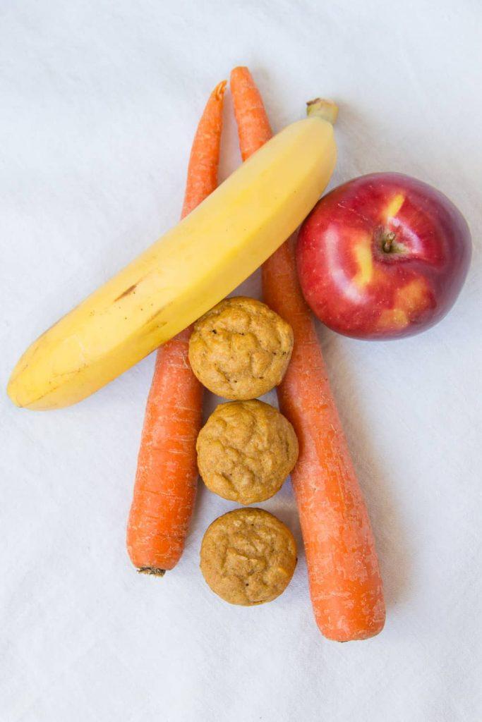 Banane Apfel Möhre Muffins ohne Zucker umrandet von einer Banane, einem Apfel und zwei Möhren