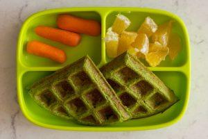 Erbsen-Pfannkuchen als Waffeln gebacken, auf einem grünen Silikonteller, mit Möhren und kleingeschnittener Orange