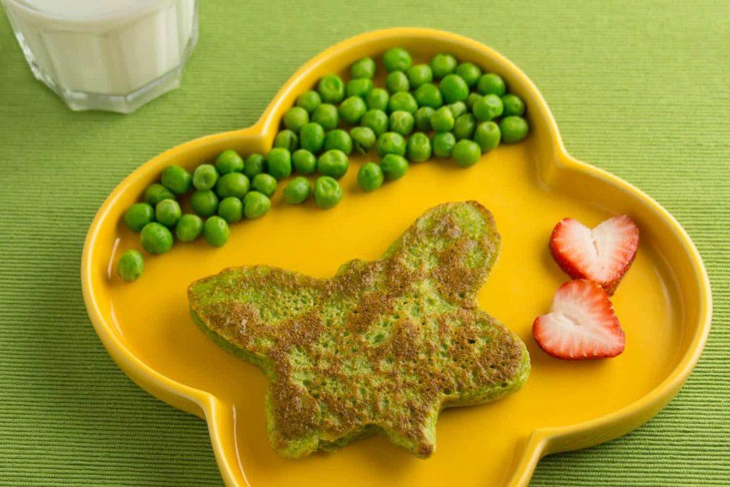 Gesunde Erbsen-Pfannkuchen auf gelbem Teller mit Erdbeeren und frischen Erbsen