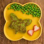Gesunde Erbsen-Pfannkuchen für Babys und Kleinkinder auf gelbem Teller mit Erdbeeren und frischen Erbsen