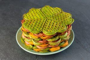 Rote, grüne und orange Waffeln auf einem grünen Teller gestapelt