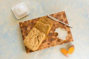 Brotlaib aufgeschnitten auf einem Holzbrett, eine Brotscheibe ist mit Butter beschmiert