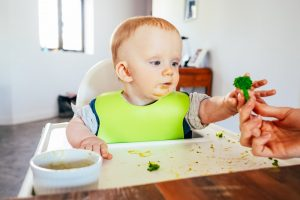 Baby im Hochstuhl, dass nach Brokkoli greift