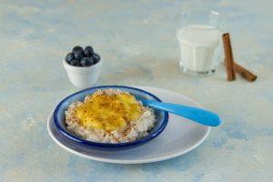 Veganer Kokos-Milchreis auf Teller, mit Mangosoße und Zimt