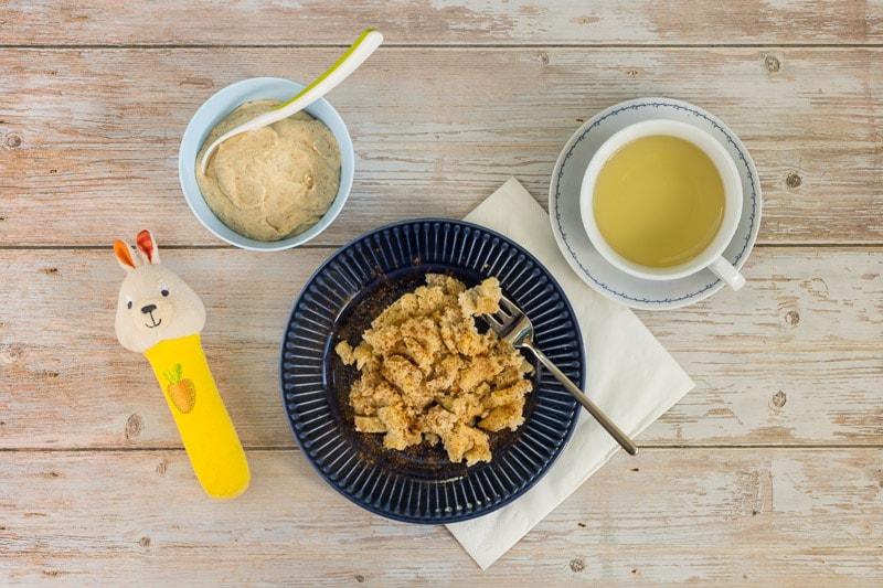 Eine Portion Apfel-Grieß-Auflauf für die Mutter, bestreut mit Zimt und Zucker und einer Tasse Tee dazu, und eine Portion des Auflaufs für das Baby püriert, als Milch-Getreide-Brei