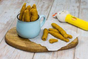 Einfache Dinkelstangen für Babys mit Süßkartoffel, auf einem Holzteller und in einem Becher