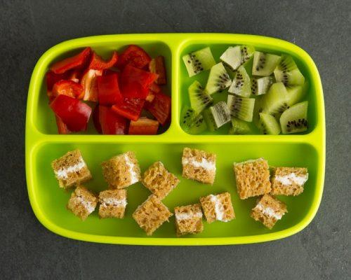 Grüner Kinderteller mit Paprika, Kiwi und Brot mit Frischkäse