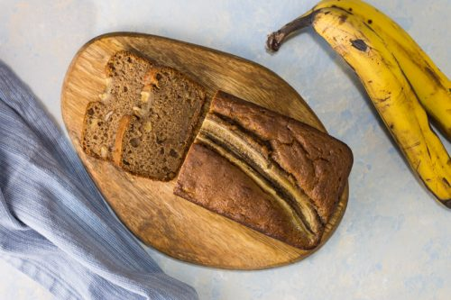 Bananenbrot ohne Zucker mit Walnüssen, aufgeschnitten auf einem Holzbrett