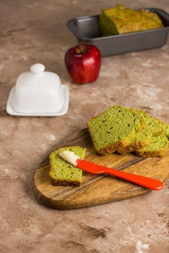 Aufgeschnittenes Erben-Brot auf einem Holzteller, mit Butter und einem Apfel im Hintergrund