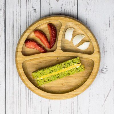 Brot ohne Hefe und Salz, mit viel Gemüse für Babys, auf einem Babyteller, mit Käse belegt, dazu Erdbeeren und Mozzarella