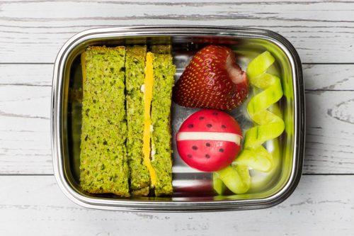 Grünes Brot ohne Hefe, mit viel Gemüse drin (Erbsen), mit Käse belegt in einer Brotdose, dazu Obst und Gemüse