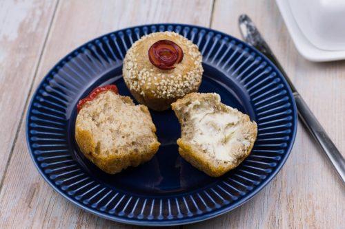 Focaccia Brötchen bzw. Muffin auf einem Teller, ein luftiges Vollkornbrötchen ist in zwei Hälften geteilt und eine Hälfte mit Butter beschmiert.