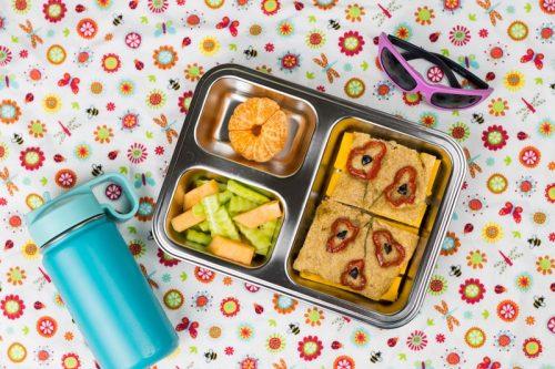 Foccacia - italienisches Vollkorn-Fladenbrot ohne Kneten mit Käse belegt, in einer Brotdose auf einer Picknick-Decke