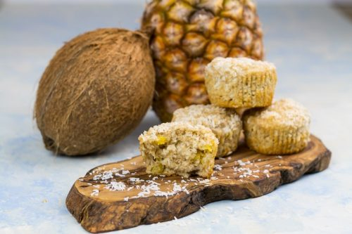 Gesunde Ananas-Muffins mit Kokos, auf einem Holzbrett, mit einer Kokosnuss und einer Ananas im Hintergrund