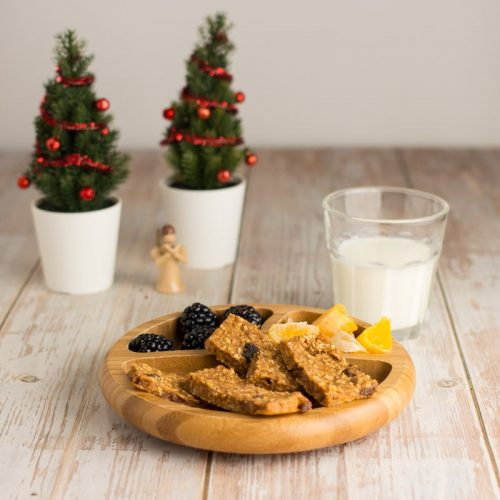 Kinder-Holzteller mit gesunden Weihnachtskeksen für Babys, Brombeeren und Organgenstücke, mit einem Glas Milch und Weihnachtsdekoration im Hintergrund
