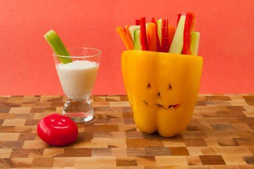 Gemüse-Sticks in einer Paprika mit Halloween-Gesicht, mit Dip und einem Babybel mit Halloween-Gesicht