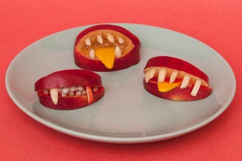 Drei Münder aus Apfel geschnitzt, mit Drakula-Zähnen und einer Käse-Zunge