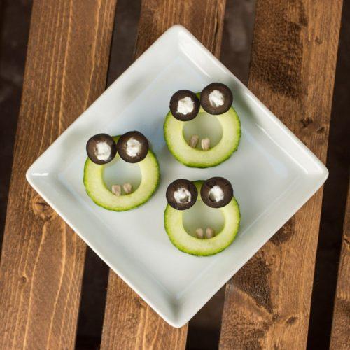 Halloween-Essen für Kinder: Gurkenscheiben zu einem erschrockenen Ohh-Gesicht dekoriert