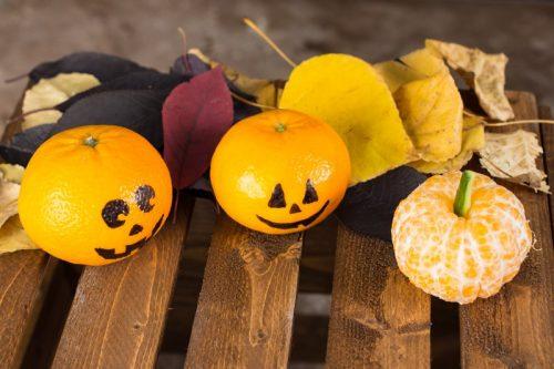 Zwei Mandarinen mit aufgemaltem Halloween-Gesicht und eine geschälte Madarine als Kürbis