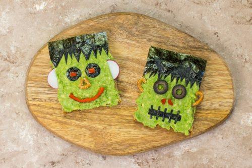 Ein Brot zu einem Frankenstein-Gesicht dekoriert, mit Avocado und weiteren Lebensmitteln