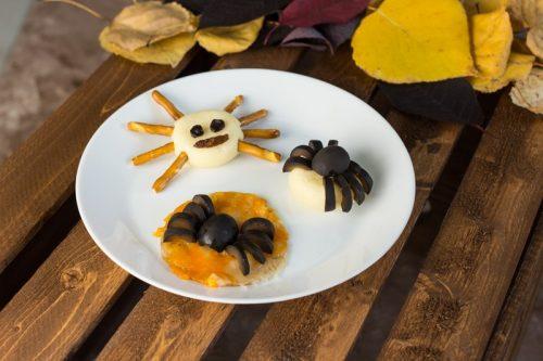 aus schwarzen Oliven geschnittene Spinnen auf einem Teller