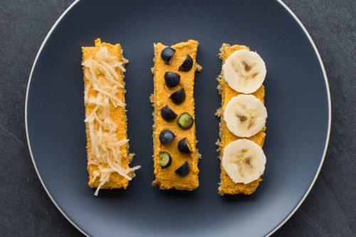 Brot mit Karotten-Aufstrich für Babys (BLW), in Streifen geschnitten und mit Banane, Blaubeere und geriebenem Apfel belegt