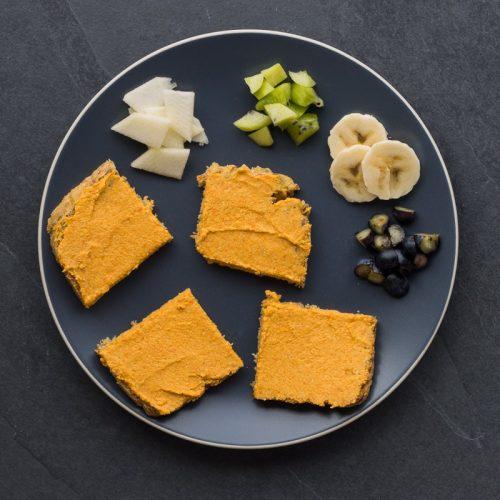 Brote mit Karotten-Aufstrich für Babys (BLW), dabenen liegt kleingeschnittenes Obst zum selber Belegen der Brote