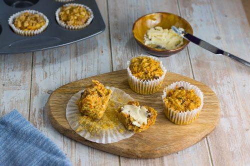 Saftige Karotten-Muffins für Kinder, auf einem Holzbrett, ein Muffin mit Butter beschmiert