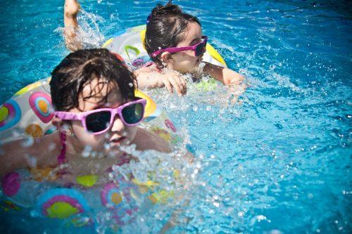zwei Mädchen mit Schwimmring im Pool