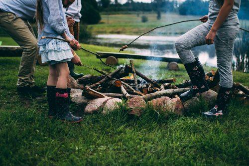 Lagerfeuer beim Campen, Kinder halten Würstchen ins Feuer