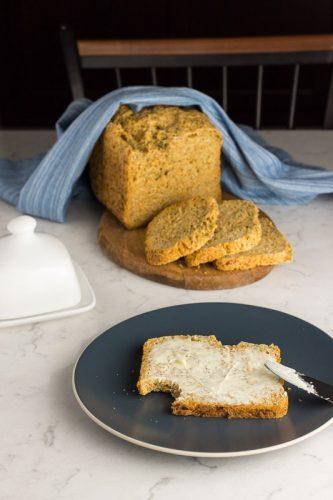 Eine Scheibe Brot mit Butter beschmiert, auf blauem Teller
