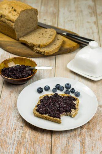 Einfaches Rezept für Vollkornbrot ohne Kneten, Brotscheibe auf einem Teller, mit Chia-Marmelade bestrichen