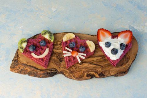 3 mit Obst zum Gesicht dekorierte Waffeln auf einem Holzbrett