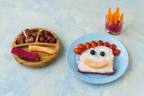 Holzteller mit Brot in BLW gerechte Stücke geschnitten und Obst, weiterer Teller mit einer Scheibe pinkem Brot, Frischkäse und einem Gesicht aus Obst und Gemüse
