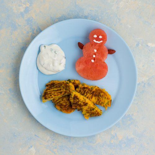 Süßkartoffelbratlinge mit Brokkoli und Parmesan, auf einem blauen Teller, mit dip und einem aus Wassermelone ausgestochenen Schneemann