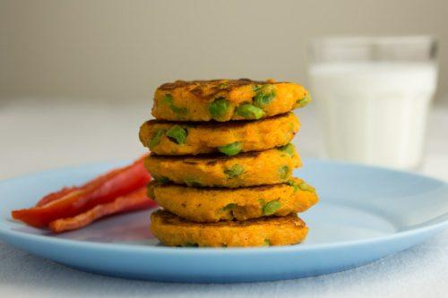 Süßkartoffel-Bratlinge mit Erbsen, zu einem Turm gestapelt, auf einem blauen Teller, mit Paprika und einem Glas Milch im Hintergrund