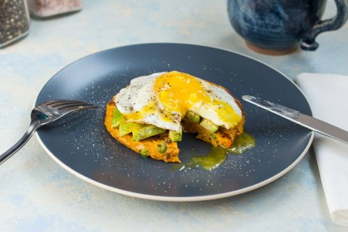 Süßkartoffel-Bratling mit Avocado und einem Spiegelei, auf einem blauen Teller