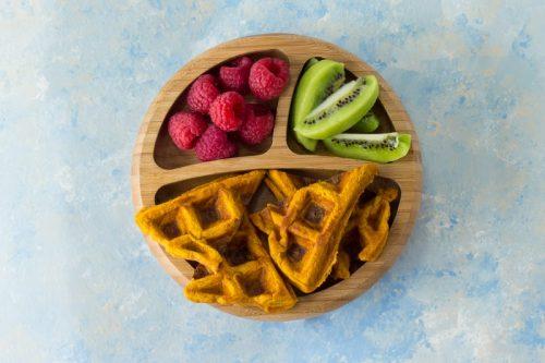 Süßkartoffelwaffeln als Beikost für Babys (BLW) auf einem Holzteller, mit Himbeeren und Kiwi