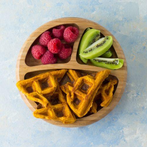 Süßkartoffel-Waffeln auf einem Holzteller, mit Himbeeren und Kiwi