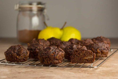 Saftige Schoko-Birne Muffins ohne Zucker auf einem Kuchengitter mit Birnen und Kakao im Hintergrund