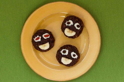 3 Schoko-Birne Muffins ohne Zucker für einen Kindergeburtstag, verziert mit einem Gesicht aus Frischkäse, Rosinen und Banane, auf einem gelben Teller