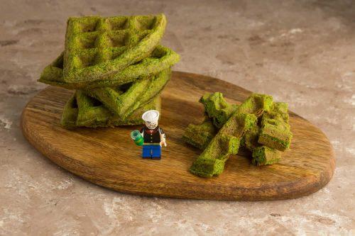 Schnelle Spinat Waffeln geviertelt auf einem Holzbrett, zusammen mit einer Lego Popeye Figur