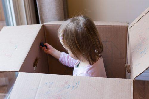 Kleines Kind sitzt in einem Umzugskarton und malt diesen von innen an