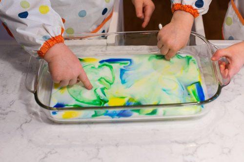 Zwei Kinder die mit einer Schale spielen, in der Milch ist und einige Tropfen Lebensmittelfarbe