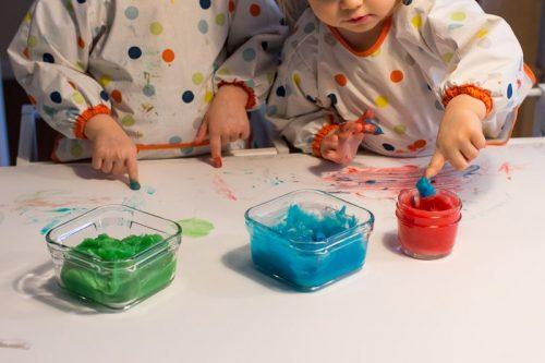 Zwei kleine Kinder, die mit Fingerfarbe malen