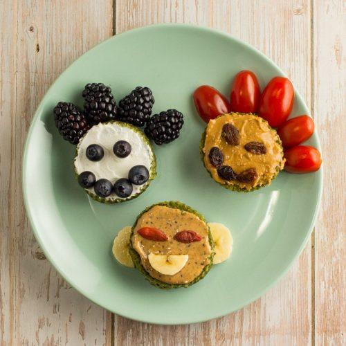 Spinat-Muffins aufgeschnitten und mit Gesichtern verziert, auf einem Teller