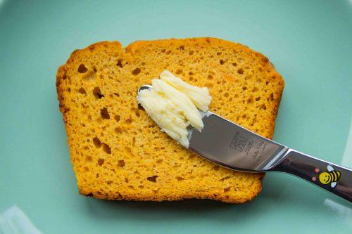 Eine Scheibe Süßkartoffelbrot und ein Messer mit Butter