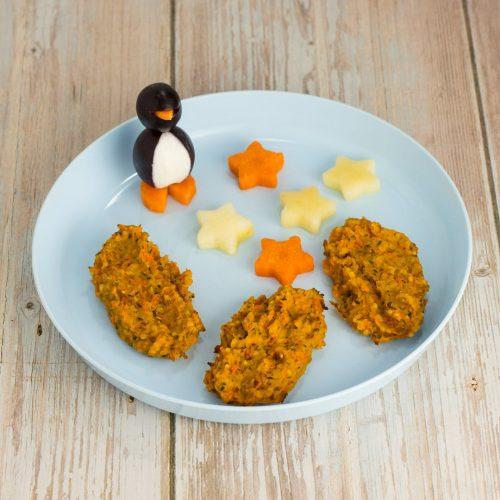 Süßkartoffel-Bratlinge mit Möhre und Hanfsamen, auf blauem Teller, mit einem Pinguin aus Weintrauben